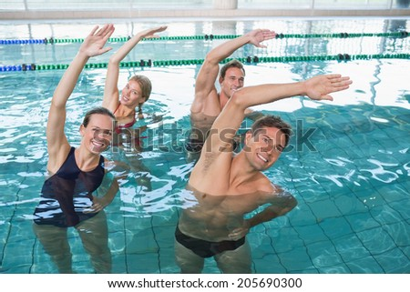 Happy fitness class doing aqua aerobics in swimming pool at the leisure centre - stock photo