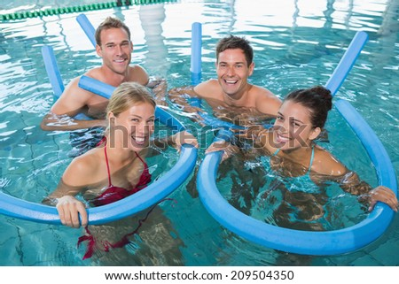Happy fitness class doing aqua aerobics with foam rollers in swimming pool at the leisure centre - stock photo