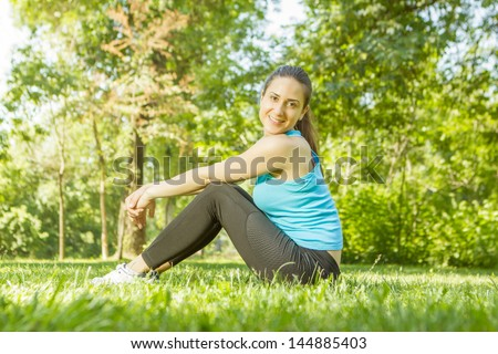 Happy fitness girl relaxing after exercising in the park.