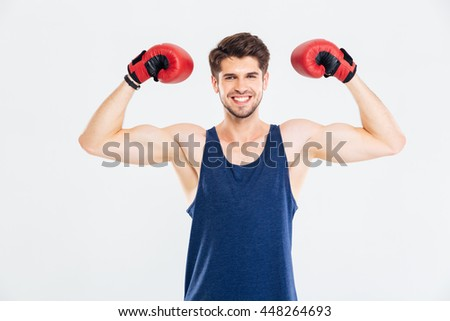 Happy fitness man standing with red boxing gloves isolated on a gray background