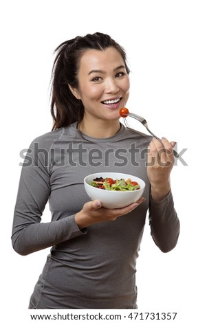 happy fitness model eating a salad shot in the studio on a white background