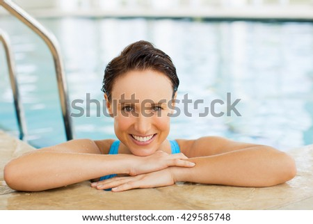 Happy fitness woman at pool - stock photo