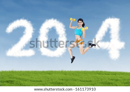Happy fitness woman jumping with shaped clouds of new year 2014 - stock photo