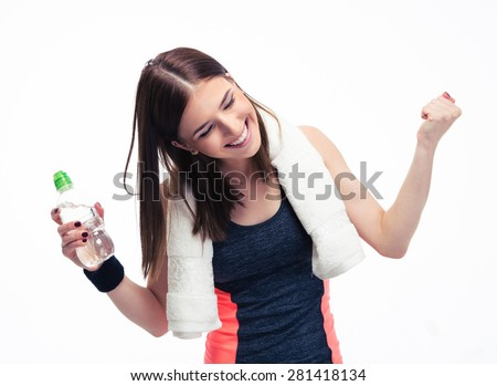 Happy fitness woman with towe and bottle of water celebrating her victory isolated on a white background. Looking at camera - stock photo