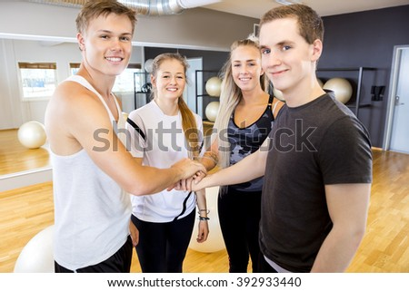 Happy fitness workout team holding hands - stock photo