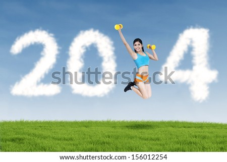 Happy fitness young woman jumping with new year 2014 of clouds - stock photo