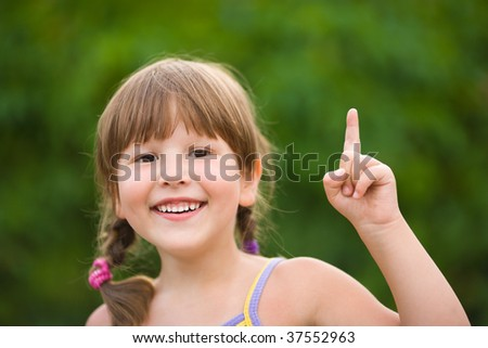 Happy five years Girl pointing up smiling outdoors - stock photo