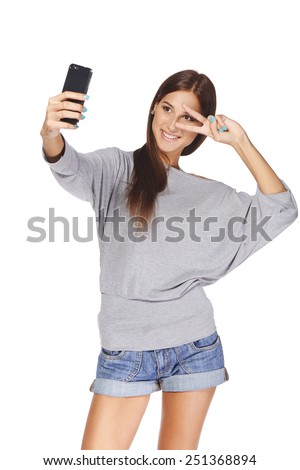 Happy flirting young girl taking pictures of herself at smart phone, over white background - stock photo