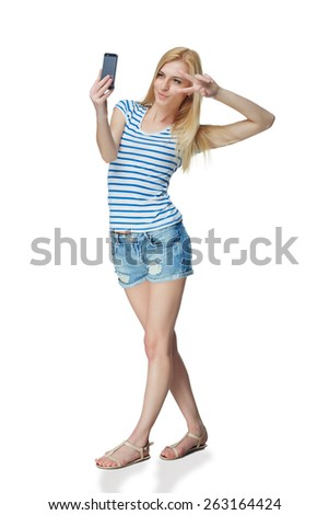Happy flirting young girl taking pictures of herself at smart phone, over white background
