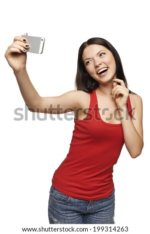 Happy flirting young girl taking pictures of herself through cell phone, over white background