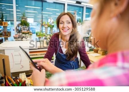 Happy florist looking at female customer using digital tablet in flower shop - stock photo