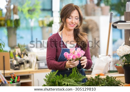 Happy florist making bouquet of pink roses in flower shop - stock photo