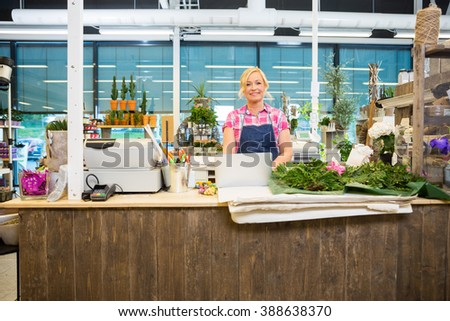 Happy Florist Standing At The Counter Of Flower Store - stock photo