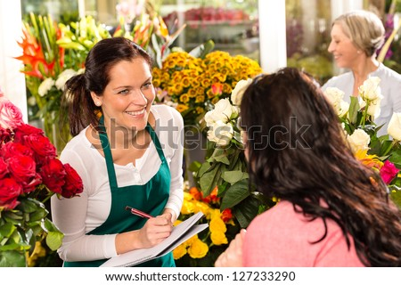 Happy florist writing flower shop talking customer woman - stock photo