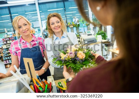 Happy florists selling rose bouquet to female customer in flower shop - stock photo