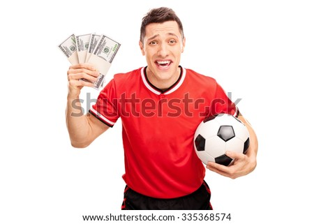 Happy football player holding a ball and a few stacks of money isolated on white background - stock photo