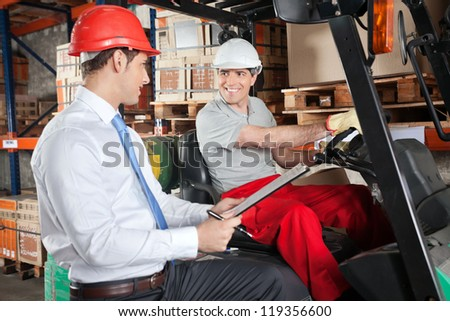 Happy forklift driver communicating with male supervisor at warehouse - stock photo