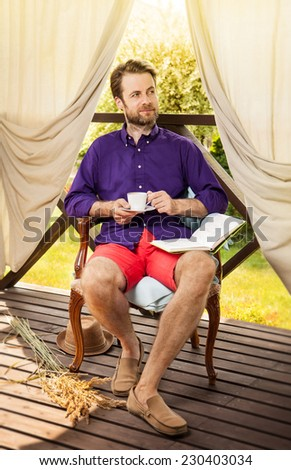 Happy forty years old caucasian man drinking morning coffee outdoor on garden terrace during sunny summer day. Countryside weekend or holiday concept. - stock photo