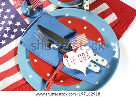 Happy Fourth of July dining table place setting in red, white and blue color theme with USA Stars and Stripes flag and heart gift tag with sample text. - stock photo