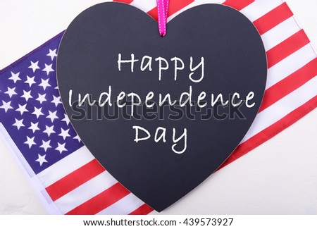 Happy Fourth of July message on heart shaped blackboard with USA Stars and Stripes flag for Independence Day greeting.