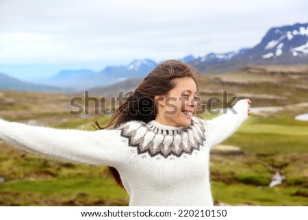 Happy free woman on Iceland in Icelandic sweater. Portrait of girl happy smiling outdoors in nature wearing Icelandic sweater. Pretty Asian Caucasian multiracial female model - stock photo