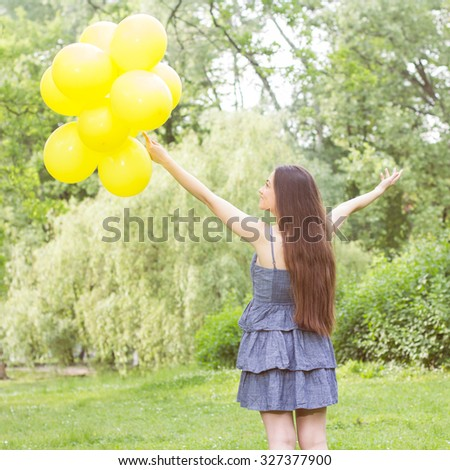 Happy, Freedom, Carefree Young Woman with Yellow Balloons at beautiful Summer Day Outdoor. Attractive female enjoying nature. - stock photo
