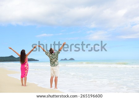 Happy freedom couple on Hawaiian beach vacations. Full length people standing with arms outstretched up to the sky showing happiness and success in Hawaii wearing traditional Aloha shirt and dress.