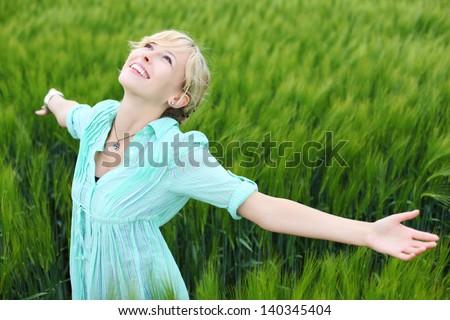 Happy fresh female enjoying the fresh air at cornfield - stock photo