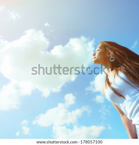 Happy fresh girl enjoying summer, youth and freedom. Toned outdoor shot against blue sky. - stock photo