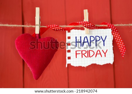 Happy Friday on instant paper and small red heart hanging on the clothesline. On red wood background - stock photo