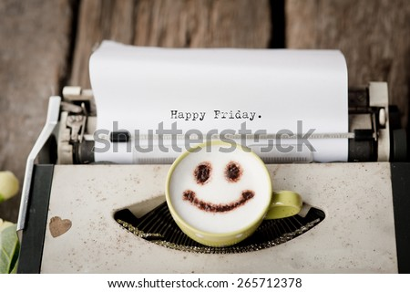 Happy Friday on typewriter with happy face coffee cup, sepia tone. - stock photo