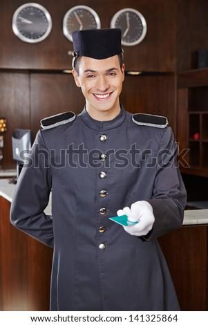 Happy friendly concierge giving hotel key card - stock photo