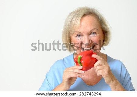 Happy friendly smiling senior lady with a fresh healthy ripe red bell pepper or capsicum in her hand in a healthy diet and nutrition concept