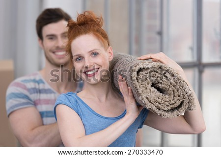 Happy friendly young woman carrying a new neutral colored carpet with her husband as they redecorate their new home - stock photo