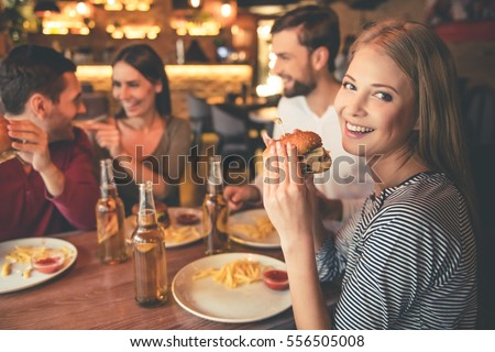 Happy friends are eating burgers, talking and smiling while spending time together in cafe