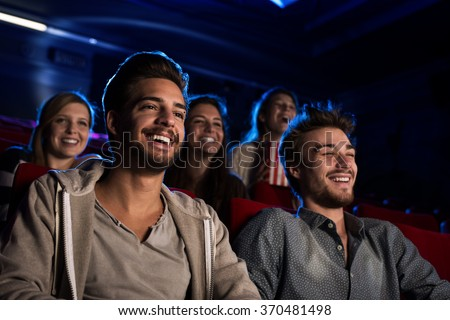 Happy friends at the cinema watching a movie together, entertainment and leisure concept - stock photo