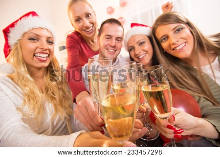 Happy friends Celebrating Christmas or New Year with glass of champagne and toasting. - stock photo