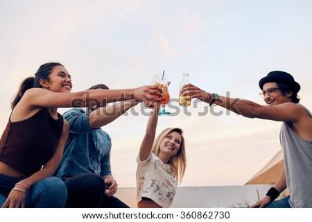 Happy friends celebrating the success with a toast at rooftop party. Young men and women toasting cocktails at party. Young people hanging out and having fun at party. - stock photo