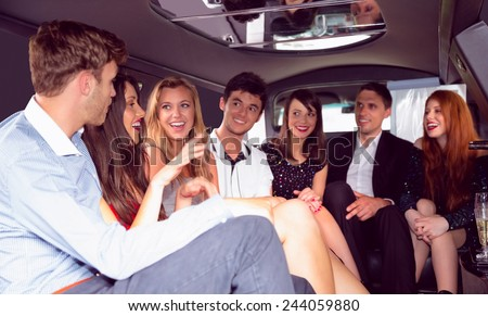 Happy friends chatting in limousine on a night out - stock photo