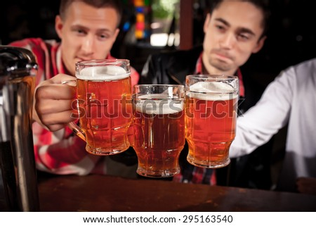 Happy friends clinking with beer mugs in pub, smiling. - stock photo