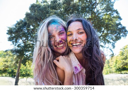 Happy friends covered in powder paint on a sunny day - stock photo