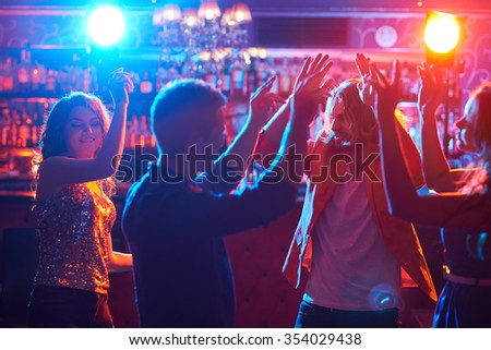 Happy friends dancing together in club