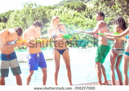 Happy friends doing water gun battle near swimming pool - stock photo
