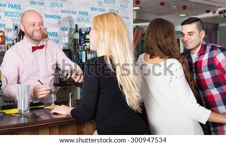 Happy friends drinking and chatting with cheerful barman at bar counter - stock photo