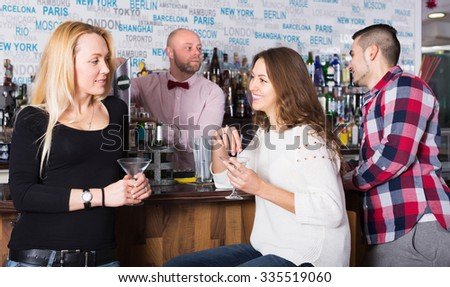 Happy friends drinking and chatting with young barman at bar counter