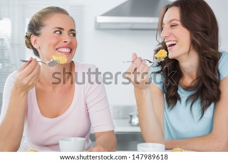 Happy friends eating cake and having coffee in the kitchen - stock photo