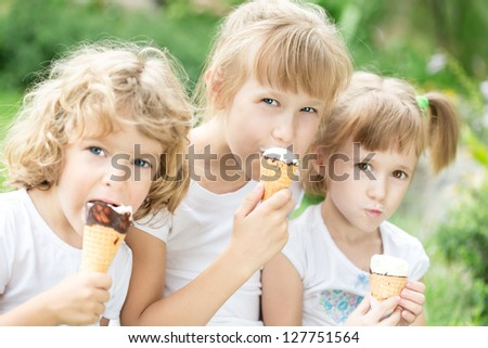 Happy friends eating ice-cream outdoors in spring park - stock photo