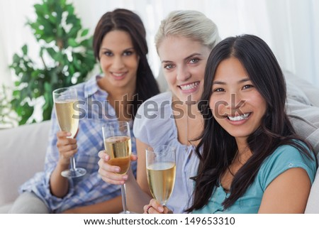Happy friends enjoying champagne together looking at camera at home on couch