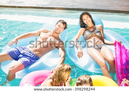 Happy friends enjoying their day together in the swimming pool - stock photo