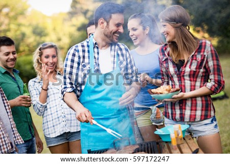 Happy friends grilling meat and enjoying barbecue party outdoors